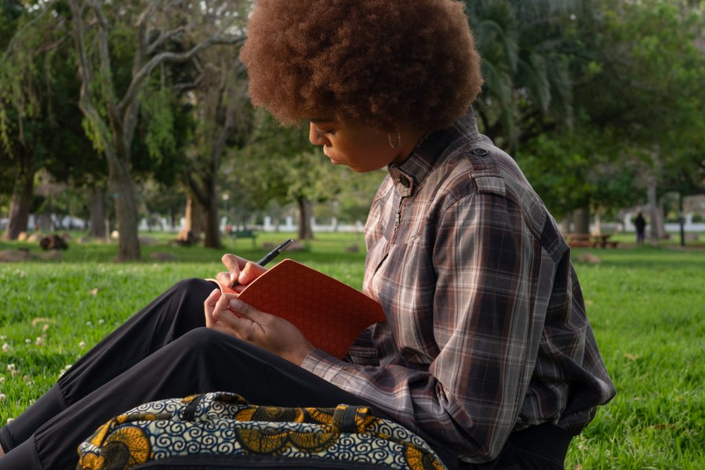 Woman with natural hair writing in notebook about her trauma